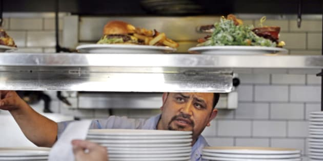 In this photo taken Tuesday, March 31, 2015, cook Alex Romero looks out from the kitchen at the Skillet Diner in Seattle. Seattle's new minimum wage law went into effect Wednesday, April 1, 2015, that will eventually raise the city's minimum wage to $15 an hour. Starting Wednesday, large businesses and national chains must raise their minimum pay to at least $11 an hour. Smaller businesses must pay at least $10 an hour. Seattle's current minimum wage is $9.47, the same as the Washington state minimum wage. (AP Photo/Elaine Thompson)