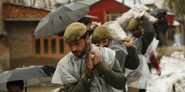 Jammu and Kashmir policemen carry sand bags to repair a breach in an embankment in a flooded area of Srinagar, Indian-controlled Kashmir, Wednesday, April 1, 2015. Although flood waters were receding, residents in the main city of Srinagar were bracing for more trouble as the meteorological office has predicted more rain over the next few days. (AP Photo/Mukhtar Khan)