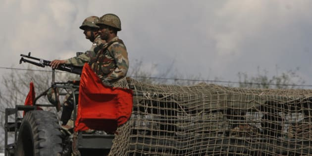 Indian army soldiers take position on a truck during an attack by suspected Kashmiri rebels near an army camp in Samba, about 48 kilometers south of Jammu, India, Saturday, March 21, 2015. Indian soldiers killed two suspected Kashmiri rebels Saturday after they tried to sneak into the army's main infantry headquarters in the Indian portion of the disputed Himalayan territory, police said. (AP Photo/Channi Anand)