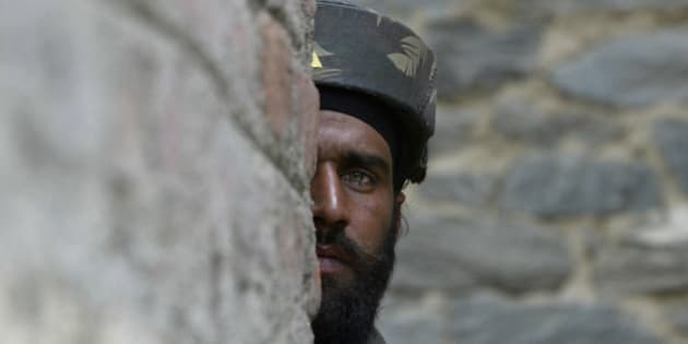 An Indian Army soldier looks on during a gun battle in Baramulla, about 55 kilometers (34 miles) north of Srinagar, India, Wednesday, April 23, 2008. Two suspected rebel commanders of the Hezb-ul-Mujahideen group were killed Wednesday in a gunbattle with government forces, police said. (AP Photo/Mukhtar Khan)