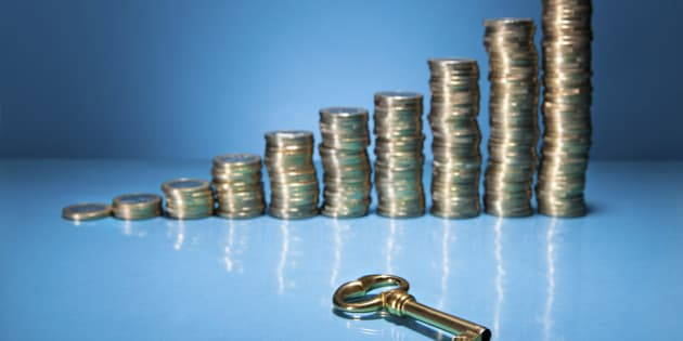 Stack Of Golden Coin And Key Over Blue Background
