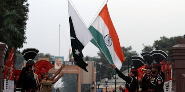 Pakistani border guards perform high kicks during a flag lowering ceremony after a Sunday suicide bombing at the Pakistan-Indian border post, in Wagah, Pakistan, Monday, Nov. 3, 2014. Pakistanis mourned on Monday for the victims of a massive suicide bombing near the border with India as the death toll from the explosion the previous day rose to at least 60, police said. (AP Photo/K.M. Chaudary)