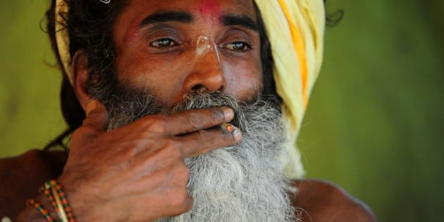 An Indian sadhu, or holy man, smokes a hand-rolled beedi cigarette as he rests near Sangam, the confluence of the rivers Ganges, Yamuna and the mythical Saraswati, on World No Tobacco Day in Allahabad on 31May,2014. The World Health Organisation (WHO) and partners mark World No Tobacco Day on May 31, highlighting the health risks associated with tobacco use.  AFP PHOTO/SANJAY KANOJIA        (Photo credit should read Sanjay Kanojia/AFP/Getty Images)