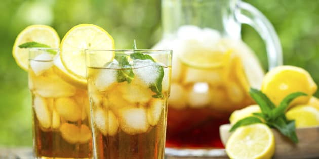 Two glasses with iced tea with lemon and ice on the wooden table