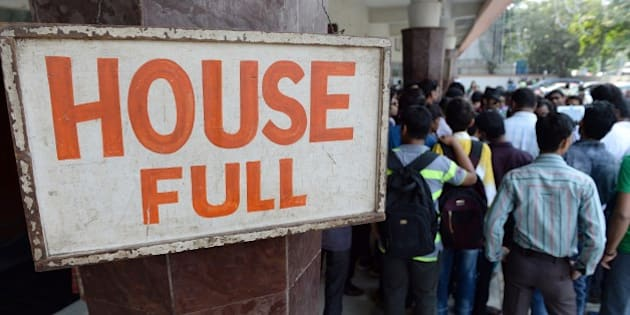 Disappointed moviegoers are seen next to a board announcing 'full house' for a screening of the popular Bollywood Hindi film 'Dilwale Dulhania Le Jayenge' (The Brave hearted Will Take The Bride Away) at the Maratha Mandir movie theatre in Mumbai on December 12, 2014. The 1995 Bollywood love flick titled Dilwale Dulhaniya Le Jayenge or 'DDLJ', as the movie is commonly known in India, is the longest running movie in Indian cinema history and clocked a successful run of 1000 weeks at the Maratha Mandir movie theatre on December 12.   AFP PHOTO / INDRANIL MUKHERJEE        (Photo credit should read INDRANIL MUKHERJEE/AFP/Getty Images)