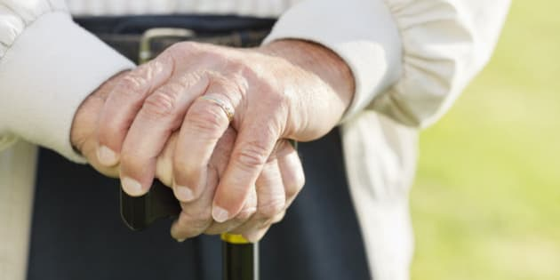 Close up of older man's hands on cane