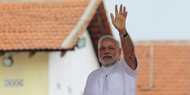 Indian Prime Minister Narendra Modi waves to the gathering during the handing over of homes under a housing scheme funded by the Indian government for war victims in Llavalai, northwest of Jaffna, Sri Lanka, Saturday, March 14, 2015. During his visit to north, Modi commissioned a section of railway track built with Indian aid in Talaimannar and ceremonially began the construction work of a cultural center to be built in the town of Jaffna with Indian assistance. Jaffna is the cultural heartland of the Tamils and was the stage of many battles during Sri Lanka's quarter century civil war. (AP Photo/Eranga Jayawardena)