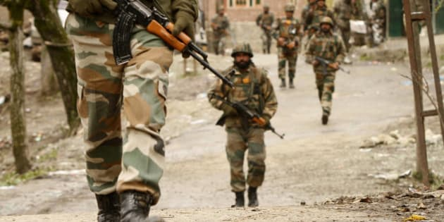 Indian Army soldiers carry out a search operation for suspected rebels during a gunbattle at Hardshoora village, 35 kilometers (20 miles) north of Srinagar, India, Thursday, April 2, 2015. Suspected Kashmiri rebels and Indian security personnel were engaged in a fierce gunbattle Thursday in the Himalayan territory, officials said. (AP Photo/Mukhtar Khan)