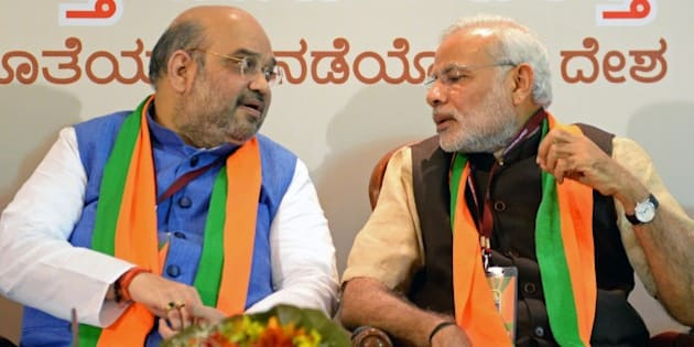 Indian Bharatiya Janata Party (BJP) national president Amit Shah (L) and Prime Minister Narendra Modi talk during a BJP office bearers' meeting held on the eve of the party's National Executive committee meeting in Bangalore on April 2, 2015. The two-day National Executive meeting, scheduled to begin on April 3, 2015 in Bangalore, will be the first such meeting since the BJP came to power last year. AFP PHOTO / Manjunath KIRAN        (Photo credit should read MANJUNATH KIRAN/AFP/Getty Images)