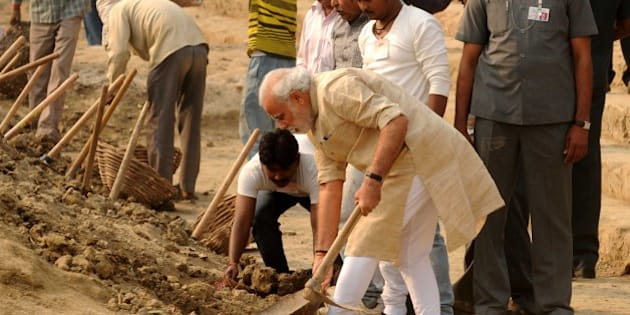 VARANASI, INDIA - NOVEMBER 8: Prime Minister Narendra Modi  using a shovel to clean Assi ghat on November 8, 2014 in Varanasi, India. Modi nominated nine persons, including chief minister Akhilesh Yadav, to carry forward the cleanliness drive in UP. After the prayers, Modi, who was accompanied by a few BJP leaders, picked up a spade and began vigorously digging the huge amount of silt that had deposited along the ghat after the rainy season. (Photo by Ashok Dutta/Hindustan Times via Getty Images)