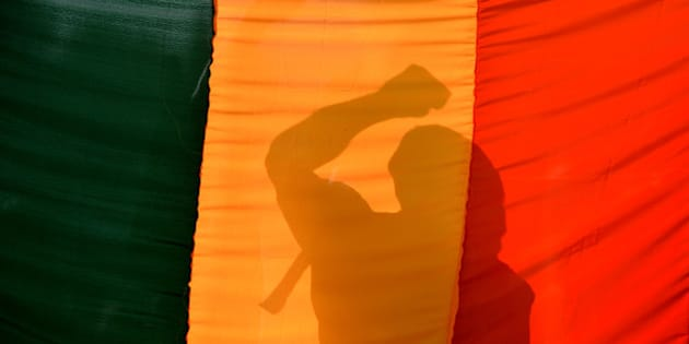 An Indian gay-rights activist gestures behind a flag during a protest against the Supreme Court ruling reinstating a ban on gay sex in Bangalore on December 11, 2013. India's Supreme Court reinstated a colonial-era ban on gay sex on that could see homosexuals jailed for up to ten years in a major setback for rights campaigners in the world's biggest democracy. AFP PHOTO/Manjunath KIRAN        (Photo credit should read Manjunath Kiran/AFP/Getty Images)
