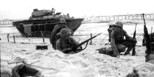 Marines moving along the beach cautiously while an amphibious tank covers them, Peleliu, Palau, September 1944. (Photo by PhotoQuest/Getty Images)