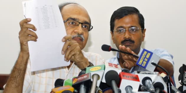Prashant Bhushan, left, and Arvind Kejriwal, associates of Anna Hazare, India's most prominent anti-corruption activist, display a list of 15 ministers serving in the present government, including its leader and Prime Minister Manmohan Singh, against whom they have prepared evidences of corruption, at a press conference in New Delhi, India, Saturday, May 26, 2012. Files containing evidences of corruption have been sent to Singh, asking him to constitute an investigation team of eminent judges to verify their claims. (AP Photo/Saurabh Das)