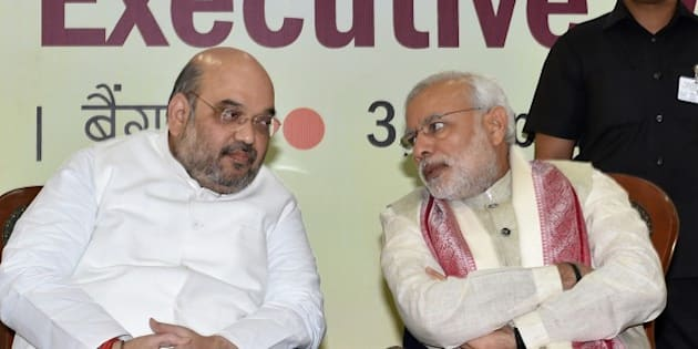 Indian Prime Minister Narendra Modi (R) and Bharatiya Janata Party (BJP) National President Amit Shah speak at a BJP National Executive committee meeting in Bangalore on April 3, 2015. AFP PHOTO/Manjunath KIRAN        (Photo credit should read MANJUNATH KIRAN/AFP/Getty Images)