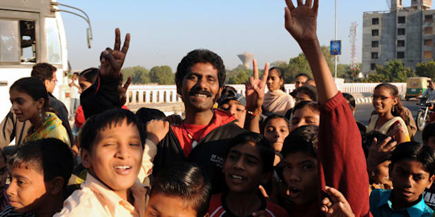 Indian mountaineer Malli Mastan Babu (C) poses with children in Ahmedabad on November 29, 2009, following a morale run with some 125 underpriviledged children and women. The 34-year old is the only South Asian to have scaled the seven highest mountain peaks in a record 172 days in 2006. AFP PHOTO/ Sam PANTHAKY (Photo credit should read SAM PANTHAKY/AFP/Getty Images)
