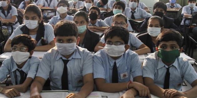 Indian students wear masks for protection against swine flu, as they attend their class at a school in Ahmadabad, Gujarat state, India, Monday, March 2, 2015. Thousands in Gujarat were tested positive for H1N1, the virus which causes swine flu. (AP Photo/Ajit Solanki)