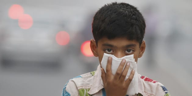 NEW DELHI, INDIA - NOVEMBER 07:  A child covers its face to take precaution from the air pollution by a mixture of pollution and fog at NCR region on November 7, 2012 in New Delhi, India. (Photo by Sanjeev Verma/Hindustan Times via Getty Images)