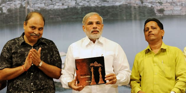 Gujarat state Chief Minister Narendra Modi (C) holds up a copy of the book 'Vadnagar- Virasat no Tasviri Vaibhav', authored by Principal Photographer of India Today Shailesh Raval (R) and India Today's Special Correspondent Uday Mahurkar (L), during a launch in Ahmedabad on October 4, 2009. Vadnagar, with its rich heritage and historical importance, is regarded as a cultural capital of the region. AFP PHOTO/ Sam PANTHAKY (Photo credit should read SAM PANTHAKY/AFP/Getty Images)