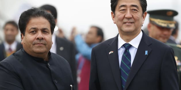 Japanese Prime Minister Shinzo Abe shakes hand with Indian Junior Minister for Parliamentary Affairs Rajeev Shukla upon arrival in New Delhi, India, Saturday, Jan. 25, 2014. Abe arrived Saturday on a three-day official visit to India and will also be the Chief Guest on India's Republic Day parade, celebrated on Jan. 26. (AP Photo/Saurabh Das)