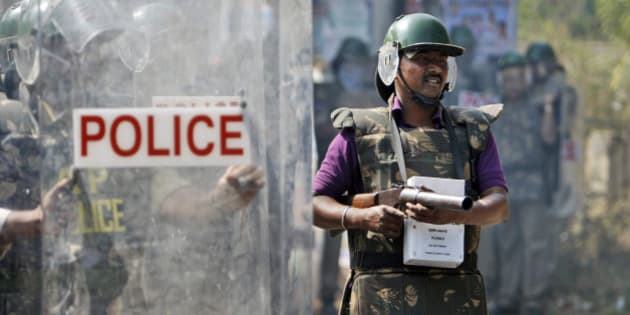 An Indian policeman prepares to throw a tear gas shell at students during a protest in Hyderabad, India, Monday, Jan. 6, 2014. A group of pro-Telangana students clashed with police at the Osmania University after they were prevented from taking out a rally towards the Andhra Pradesh state assembly. The students demanded that the Telangana bill should be taken up for discussion in the ongoing session of the assembly. (AP Photo/Mahesh Kumar A.)