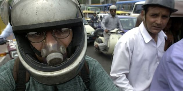 NEW DELHI, INDIA:  A Delhi motorcyclist wears an air-filter while waiting for the light to change at a downtown crossing, 05 June 2000 in New Delhi.  India was rated the worst country in Asia for air, water and noise pollution by a private think-tank.  The world celebrates Environment Day 05 June. (ELECTRONIC IMAGE) AFP PHOTO JOHN MACDOUGALL (Photo credit should read JOHN MACDOUGALL/AFP/Getty Images)