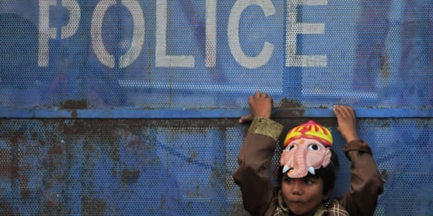 An Indian boy wearing a mask of elephant-headed Hindu god Ganesha leans against a police barricade and watches devotees taking statues of Ganesha in a procession for immersion  on the final day of the festival of Ganesh Chaturthi in Hyderabad, India, Monday, Sept. 8, 2014. Every year millions of devout Hindus immerse Ganesh idols into oceans and rivers during the ten-day long festival that celebrates the birth of Ganesha. (AP Photo/Mahesh Kumar A.)