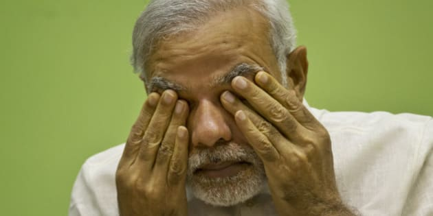 India's Prime Minister Narendra Modi rubs his eye as he attends a conference by The Environment Ministry in New Delhi, India, Monday, April 6, 2015. Modi launched Monday National Air Quality Index for 10 cities in India during the national conference. Experts say India's index falls short of international standards by using a formula that downplays how dangerous the air quality is on any given day. (AP Photo/Saurabh Das)