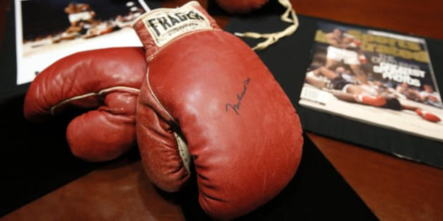 """The boxing gloves of Muhammad Ali, front, and of Sonny Liston, rear, sit on a table at Heritage Auctions by a photo and magazine depicting a moment captured during the fight, Thursday, Jan. 22, 2015, in Dallas. The 1965 rematch between Ali and Liston remains one of the most controversial sporting events of the 20th century. To this day, 50 years later, questions swirl. Was it a knockout or """"phantom punch"""" that Ali threw when he decked Liston minutes into the first round of their heavyweight title fight. (AP Photo/Tony Gutierrez)"""