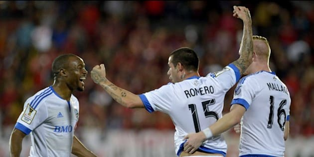 Impact of Montreal  players Reo Coker (L),  Andres Romero (C) and  Callum Mallace (R) celebrate a goal against Liga Deportiva Alajuelense during their Concacaf Champions League semifinal match in Alejandro Morera Soto stadium in Alajuela, 25km northwest of San Jose on April 7, 2015. AFP PHOTO/Ezequiel BECERRA        (Photo credit should read EZEQUIEL BECERRA/AFP/Getty Images)