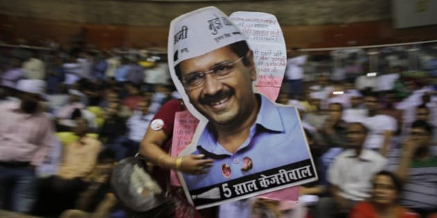 A supporter carries cut-outs of Delhi Chief Minister Arvind Kejriwal during a ceremony to launch an anti-corruption helpline in New Delhi, India, Sunday, April 5, 2015. (AP Photo/Altaf Qadri)
