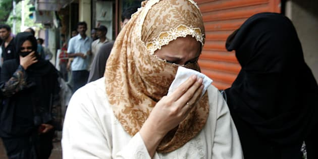 Raheen Memon, center, wife of Yakub Memon, reacts as she arrives at a special court trying cases of the 1993 Mumbai bombings that killed 257 people in Mumbai, India, Friday, July 27, 2007. Justice Pramod Kode handed down the death penalty to brother of Tiger Memon, Yakub and said he was one of the key persons who arranged for weapons and arms training and for storing explosives used in the March 12, 1993 blasts. (AP Photo/Rajesh Nirgude)