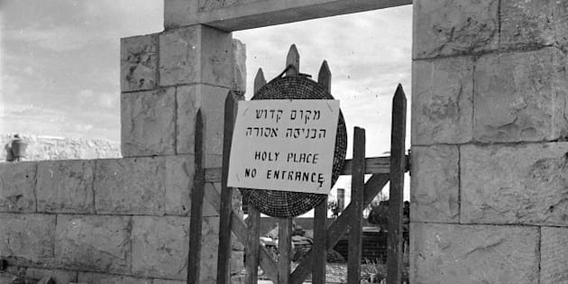 """This is the entrance to a cemetery of Deir Yassin notable citizens before the massacre of the villagers in April 1948.  The Jews who know occupy the land have put up a sign in Hebrew and English that reads """"Holy Place.  No Entrance.""""  (AP Photo)"""