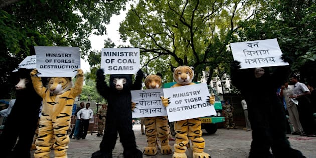 Greenpeace activists dressed as bears and tigers hold placards during a protest, urging the government to stop using the corruption-induced coal shortage as an alleged reason to mine in forest areas, outside the Coal Ministry  in New Delhi on September 11, 2012.  Indian police have opened a probe into five coal companies after raiding premises across the country over the alleged misallocation of lucrative mining rights. AFP PHOTO/ MANAN VATSYAYANA        (Photo credit should read MANAN VATSYAYANA/AFP/GettyImages)