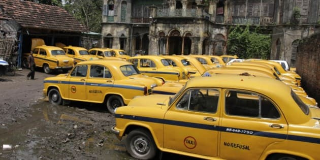 Ambassador cars, converted to yellow cabs are parked in front of a century old building during a daylong taxi strike in Kolkata, India, Wednesday, Sept. 10, 2014. The strike was called by the left party unions demanding fare hike and to protest alleged police atrocities. (AP Photo/ Bikas Das)