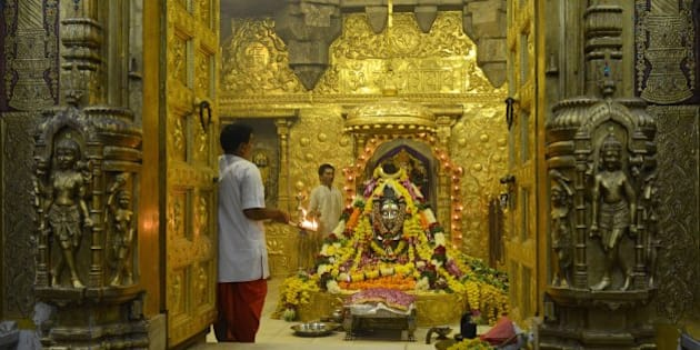 Indian Hindu priests perform the 'Aarti' religious ritual at the Somnath temple, recently decorated by gold plating, located in the Prabhas Patan near Veraval in Saurashtra, some 350 kms from Ahmedabad on the occasion  of Kartika Poornima (Full Moon Day ) on November 17, 2013. Karthik, the eighth lunar month of the Hindu calendar, is considered to be one of the holiest months and thousands of Hindu devotees pray and take dips in holy rivers at various places on the occasion of the Kartik Purnima festival - full moon day - which falls on November 17 this year. AFP PHOTO / Sam PANTHAKY        (Photo credit should read SAM PANTHAKY/AFP/Getty Images)