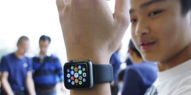 A customer tries on an Apple Watch at an Apple Store in Hong Kong Friday, April 10, 2015. From Beijing to Paris to San Francisco, the Apple Watch made its debut Friday. Customers were invited to try them on in stores and order them online. (AP Photo/Kin Cheung)