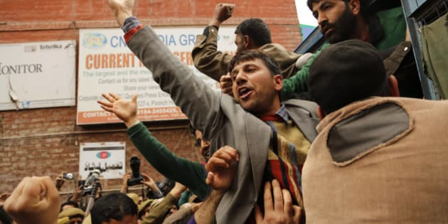 In this Wednesday, April 8, 2015 photo, Kashmiri government teacher shout slogans after being detained during a protest in Srinagar, Indian controlled Kashmir. Police detained dozens of government teachers during a protest alleging they have not been paid salaries for several months. (AP Photo/Mukhtar Khan)
