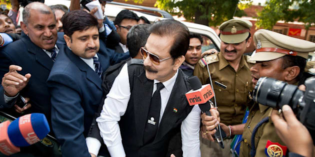 Security officials escort India's Sahara group chairman Subrata Roy (C) on his arrival at the Supreme Court in New Delhi on March 4, 2014.  Black ink was thrown on Sahara chairman Subrata Roy's face as he arrived at the Supreme Court , escorted by police personnel. The attacker, who managed to get close to Roy in the crowd and threw black ink on him, claimed to be Manoj Sharma, a lawyer from Gwalior, Madhya Pradesh.  Roy was arrested after he failed to respond to the Supreme Court's summons to appear in court in connection with the case in which Sahara owes millions of investors over 22,000 crore Indian rupees (3.5 billion dollars). AFP PHOTO/Prakash SINGH        (Photo credit should read PRAKASH SINGH/AFP/Getty Images)