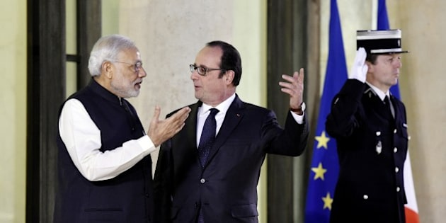 French President Francois Hollande (C) welcomes Indian Prime Minister Narendra Modi (L) upon his arrival for an official dinner at the Elysee palace in Paris on April 10, 2015, as part of Modi's official visit in France.  India's prime minister announced that New Delhi had ordered 36 Rafale fighter jets from France in a multi-billion-euro agreement that has been years in the making. Standing alongside his counterpart Francois Hollande on a visit to France -- the first leg of his maiden trip to Europe -- Narendra Modi finally relieved the frantic speculation over whether tortuous, years-long negotiations on buying the jets would ever bear fruit.  AFP PHOTO/ ALAIN JOCARD        (Photo credit should read ALAIN JOCARD/AFP/Getty Images)