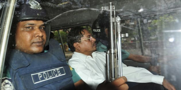 Muhammad Kamaruzzaman, assistant secretary-general of the hardline Islamic party Jamaat-e-Islami, leaves a court escorted by policemen in Dhaka, Bangladesh, Thursday, May 9, 2013. A Bangladesh tribunal convicted the top Islamic party politician Thursday of atrocities stemming from the nation's 1971 independence war and sentenced him to death, triggering fears of another wave of deadly street violence between party supporters and security forces. (AP Photo/Khurshed Rinku)
