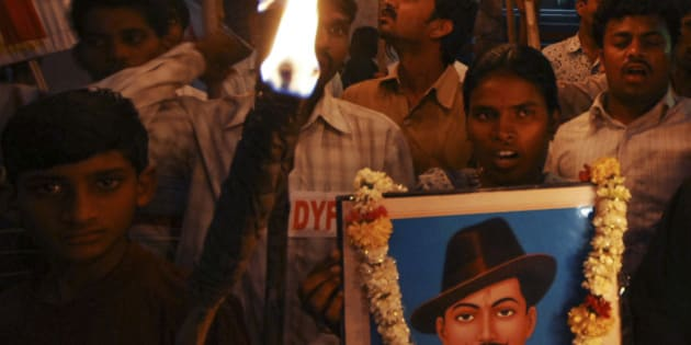Members of Democratic Youth Federation of India and Students Federation of India hold a photograph of Bhagat Singh as they participate in a torch rally to pay tribute to Indian freedom fighters Bhagat Singh, Sukhdev and Rajguru who were hanged to death by the British on March 23, 1931, in Hyderabad, India, Monday, March 23, 2009. (AP Photo/Mahesh Kumar A)