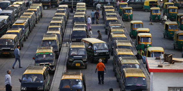 In this Monday, March 24, 2014 photo, traditional black-and-yellow licensed cabs stand parked waiting for customers at a railway station in New Delhi, India. Most licensed taxis are banned from having air conditioning under an archaic municipal rule, leaving passengers suffering with rolled-down windows in suffocating heat and noxious pollution. Taxi-hailing smartphone app Uber is making a big push into Asia with the company starting operations in 18 cities in Asia and the South Pacific including Seoul, Shanghai, Bangkok, Hong Kong and five Indian cities in the last year. (AP Photo/Saurabh Das)