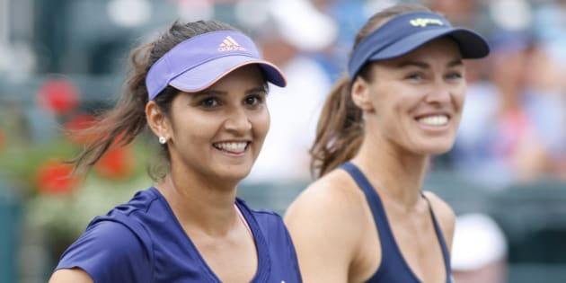 Sania Mirza, left, of India, celebrates with her teammate, Martina Hingis, of Switzerland, after defeating Alla Kudryavtseva and Anastasia Pavlyuchenkova during a doubles final match at the Family Circle Cup tennis tournament Sunday, April 12, 2015, in Charleston, S.C. Mirza and Hingis won 6-0, 6-4. (AP Photo/Mic Smith)
