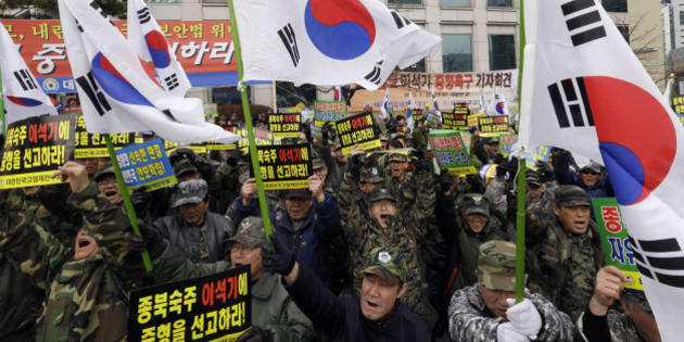 """South Korean Vietnam War veterans with national flags shout slogans during a rally denouncing former Unified Progressive Party lawmaker Lee Seok-ki  near the Supreme Court in Seoul, South Korea, Thursday, Jan. 22, 2015. South Korea's Supreme Court on Thursday upheld a prison sentence for  Lee arrested for encouraging an armed rebellion in the South should war with North Korea break out. The letters on placards read """" Punish Lee Seo-ki."""" (AP Photo/Ahn Young-joon)"""