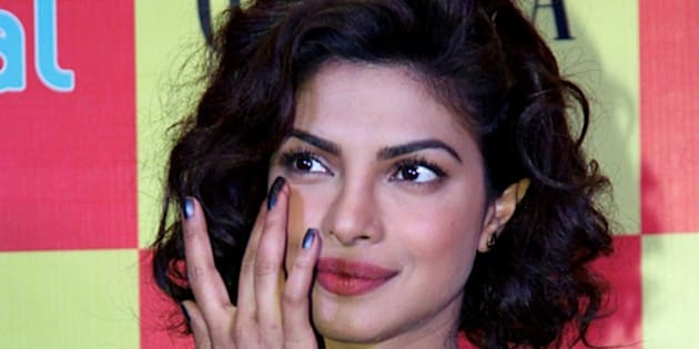 Indian Bollywood film actress Priyanka Chopra poses during the launch of the latest Grazia magazine cover in Mumbai on December 17, 2014.   AFP PHOTO        (Photo credit should read STR/AFP/Getty Images)