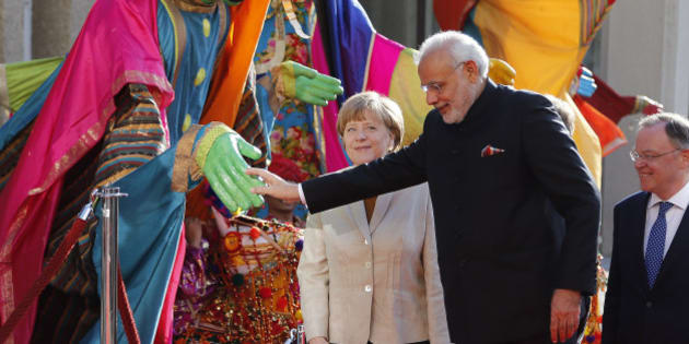 German Chancellor Angela Merkel, center, welcomes India's Prime Minister Narendra Modi,  second right, as a traditional Indian music group performs at the opening of the industrial fair in Hanover, Germany, Sunday, April 12, 2015. India is this years' partner country and participates in one of the worlds biggest industrial fairs  that lasts till April 17,2015. (AP Photo/Frank Augstein)