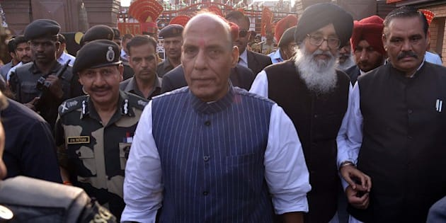 Union Home Minister Rajnath Singh (C), Punjab state chief minister Parkash Singh Badal (2R) and Border Security Force (BSF) Director General DK Pathak (L) walk during the closing ceremony for the Camel Safari expedition in Amritsar on March 22, 2015. In a joint venture by the BSF and Tata Steel Adventure Foundation (TSAF), 20 women are participating in the expedition which is a part of the BSF's Golden Jubilee celebrations.  The expedition started from Bhuj in the state of Gujarat and will culminate at India-Pakistan Wagah border post on March 22, after travelling some 2300 kms.  AFP PHOTO / NARINDER NANU        (Photo credit should read NARINDER NANU/AFP/Getty Images)