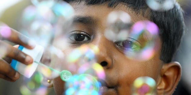 A Sri Lankan child plays with bubbles at the main zoo in Colombo on October 1, 2013. Sri Lanka is marking the International Day of Children with a series of state-sponsored events to focus on eradicating child labour and the sexual abuse of children. AFP PHOTO/ LAKRUWAN WANNIRACHCHI        (Photo credit should read LAKRUWAN WANNIARACHCHI/AFP/Getty Images)