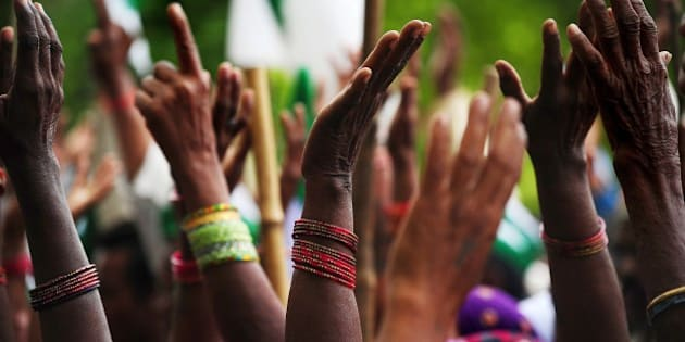 Indian farmers of the Bharatiya Kisan Union (BKU) - Indian Farmers' Union - raise their hands as they listen to spoeeches during a protest demanding compensation for damage to crops due to fluctuating rains and the waiving of electricity bills and loan interest, in Allahabad on April 7, 2015.  AFP PHOTO / SANJAY KANOJIA        (Photo credit should read Sanjay Kanojia/AFP/Getty Images)
