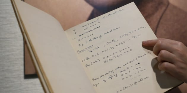 FILE - In this March 19, 2015, file photo, a page from the notebook of British mathematician and pioneer in computer science Alan Turing, the World War II code-breaking genius, is displayed in front of his portrait during an auction preview in Hong Kong. The 56-page manuscript, containing Turing's complex mathematical and computer science notations, is being sold by Bonhams in New York on Monday, April 13. (AP Photo/Kin Cheung, File)